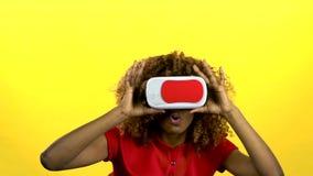 O mulato em vidros da realidade virtual está olhando um vídeo interessante Fundo amarelo Movimento lento vídeos de arquivo