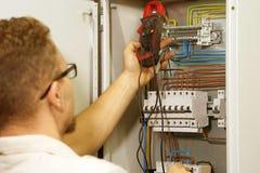 O multímetro está nas mãos do eletricista no fundo do armário bonde da automatização Ajuste do circuito de controle elétrico para foto de stock