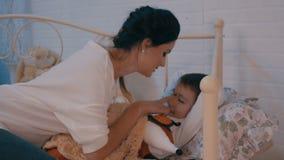 O mum agradável dá um beijo dianteiro a seu bebê antes do sono e cobre-a muito docemente com uma cobertura video estoque