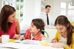O Mum ajuda crianças com trabalhos de casa enquanto o paizinho trabalha Fotografia de Stock