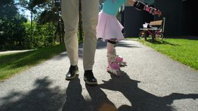O Mum ajuda sua filha pequena a patinar em patins de rolo filme