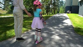 O Mum ajuda sua filha pequena a patinar em patins de rolo video estoque