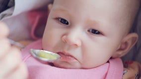 O Mum alimenta com uma colher seu puré recém-nascido bonito do bebê do close up do abobrinha vídeos de arquivo