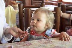 O Mum alimenta a criança Imagens de Stock Royalty Free