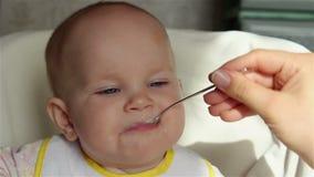 O Mum alimenta a criança com uma colher do papa de aveia video estoque