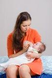 O Mum alimenta da filha da garrafa que senta-se em uma cama Imagens de Stock