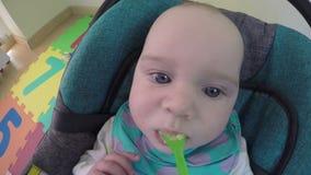 O Mum alimenta a menina de uma colher com a batata de erva-benta do fruto 4K vídeos de arquivo