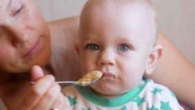 O Mum alimenta o bebê bonito com um papa de aveia do fruto da colher A criança olha a certo ponto com cuidado Close-up vídeos de arquivo