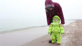 O Mum anda com a criança em uma praia no inverno Primeiras etapas video estoque