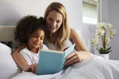 O mum caucasiano e a filha preta leram um livro junto na cama Fotografia de Stock