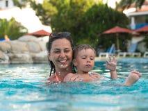 O Mum com a criança banha-se na associação em férias fotografia de stock