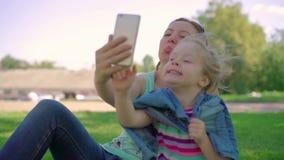 O Mum com uma filha pequena faz o selfie video estoque