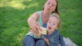 O Mum com uma filha pequena faz o selfie vídeos de arquivo