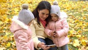 O Mum e duas filhas no parque que olha o telefone no outono estacionam vídeos de arquivo