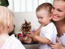 O Mum e os miúdos sentam-se perto de uma pele-árvore do Natal imagem de stock royalty free