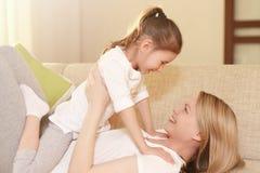 O Mum e sua menina bonito da criança da filha estão jogando, estão sorrindo e estão abraçando Mother& feliz x27; dia de s Imagens de Stock Royalty Free