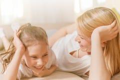 O Mum e sua menina bonito da criança da filha estão jogando, estão sorrindo e estão abraçando Mother& feliz x27; dia de s Imagens de Stock