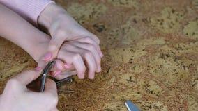 O Mum está cortando a raigota a seu filho por Clippers no backgound de madeira e está arquivando-o pregos Mãos do close-up filme