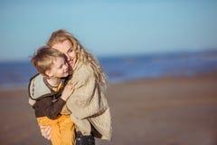 O mum está mantendo seu filho em no suas mãos e sorriso Imagens de Stock Royalty Free