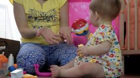 O Mum joga com uma criança pequena em uma sala no assoalho video estoque