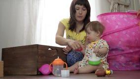 O Mum joga com uma criança pequena em uma sala no assoalho filme