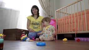O Mum joga com uma criança pequena em uma sala no assoalho vídeos de arquivo