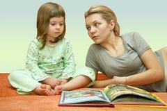 O Mum lê um conto de fadas à criança Imagens de Stock Royalty Free