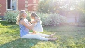 O mum novo abraça uma filha no gramado filme