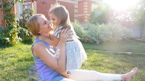 O mum novo abraça uma filha no gramado vídeos de arquivo