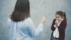 O Mum que grita em sua filha, mostrando a seu punho o conceito da educação não é uma filha organizada video estoque