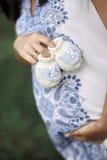 O mum tornando-se guarda sapatas pequenas em sua barriga Fotos de Stock Royalty Free