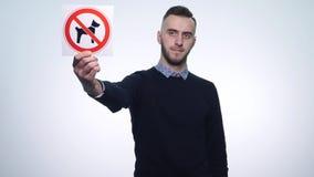 O ` não é permitido ao homem novo que guarda cães do ` dos sinais em um fundo branco filme