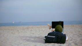 O nômadas milenar trabalha no portátil na praia vídeos de arquivo