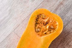 O núcleo com sementes cortou a abóbora ao meio no fundo da textura de madeira, close-up imagem de stock