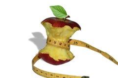 O núcleo de uma maçã vermelha envolvida em uma fita de medição em um fundo branco fotografia de stock