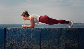 O núcleo desportivo do treinamento da mulher muscles na praia imagem de stock royalty free