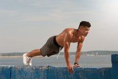 O núcleo do treinamento do homem novo muscles na praia imagens de stock royalty free