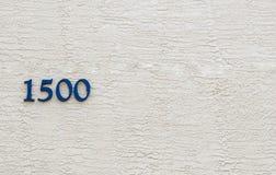 O número 1500 contra uma parede do estuque imagem de stock royalty free