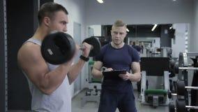 O número pessoal das contagens do instrutor de homem dos exercícios tem com um barbell no bíceps video estoque