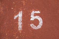 O número quinze no branco em uma parede vermelha velha fotografia de stock