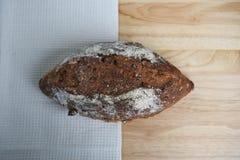 O naco caseiro do pão do artesão cozeu recentemente em uma placa de corte de madeira com toalha de mesa de creme da cor Imagens de Stock Royalty Free