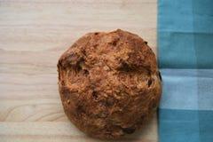 O naco caseiro do pão do artesão cozeu recentemente em uma placa de corte de madeira com toalha de mesa verde da verificação Fotos de Stock
