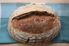 O naco caseiro do pão do artesão cozeu recentemente em uma placa de corte de madeira com toalha de mesa verde da verificação Fotografia de Stock