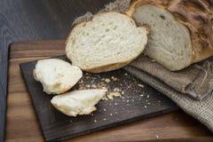 O naco de pão rústico recentemente cozido no ajuste da casa da quinta com corteja Fotografia de Stock Royalty Free