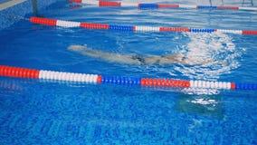 O nadador fêmea alcança a extremidade de uma pista, a seguir empurra-a para trás 4K filme