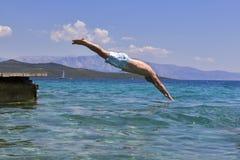 O nadador que salta à água do mar foto de stock