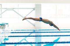 O nadador que salta do bloco começar me Imagem de Stock Royalty Free