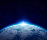 O nascer do sol azul da terra do planeta sobre o oceano nebuloso com protagoniza no céu Foto de Stock