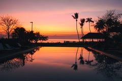 O nascer do sol bonito com a palmeira do coco da silhueta e a piscina no hotel de luxo bonito recorrem Imagem de Stock Royalty Free