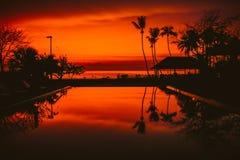 O nascer do sol bonito com a palmeira do coco da silhueta e a piscina no hotel de luxo bonito recorrem Fotografia de Stock Royalty Free